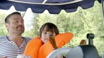 padre e figlio godono di un giro in barca sul fiume girato al rallentatore video