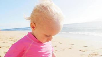 chapeau de bébé blond mignon se fait sauter sur une plage