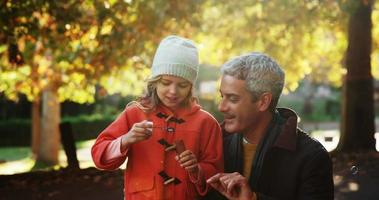 garota soprando bolhas segurando pelo pai ao ar livre
