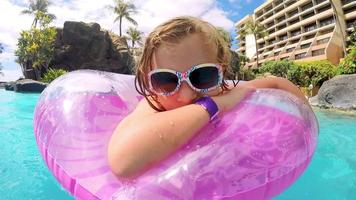 carina ragazza bionda che nuota in una piscina del resort con un giocattolo gonfiabile