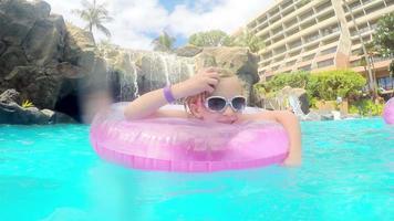 linda garota loira nadando na piscina de um resort com um brinquedo inflável