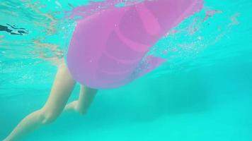 süßes blondes Mädchen, das in einem Resortpool mit einem aufblasbaren Spielzeug schwimmt