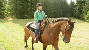junges Mädchen, das ein Pferd in einem Wald reitet
