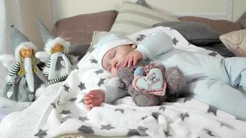 child sleeping on parents' bed in a cozy atmosphere in the house, little boy asleep hugging a stuffed toy, sweet baby sleep in the winter season video