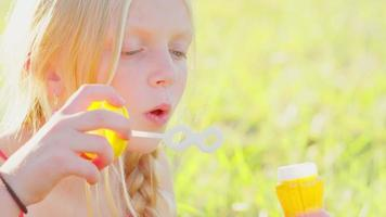 joven rubia soplando burbujas afuera