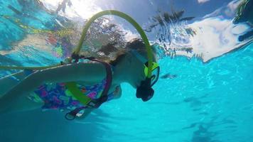 Linda chica rubia nadando en una piscina con equipo de buceo