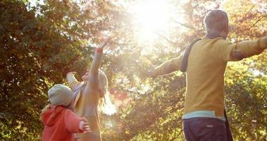garota virando com os pais, tudo com as mãos para cima