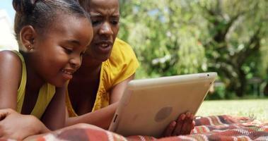 Portrait de jolie mère et fille utilisent une tablette dans le jardin