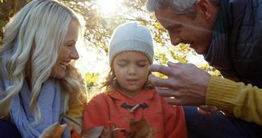 mãe pai e filha brincando com folhas ao ar livre