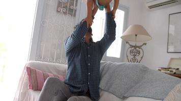 Vater und Sohn spielen zusammen auf dem Sofa video