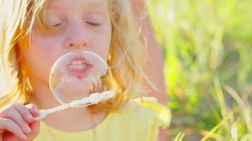 giovane ragazza bionda che soffia bolle di fuori video