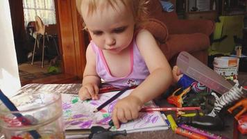 dulce niña dibuja con lápices de colores