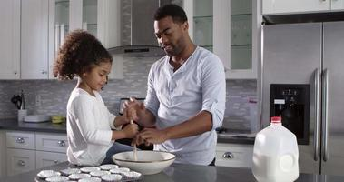 Black dad and his young daughter baking together at home, shot on R3D