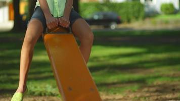 jovem em uma gangorra em um parque video