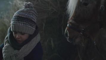 kleines Mädchen bereitet Stroh für Pony vor video