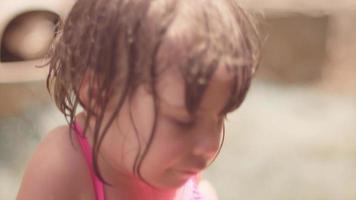 Nahaufnahme eines niedlichen kleinen Mädchens mit nassen Haaren, die draußen spielen und dumme Gesichter machen