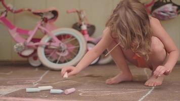 una giovane ragazza disegna un cuore per terra con il gesso