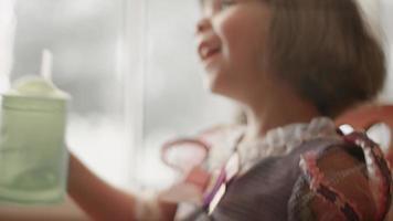 uma menina com um vestido de princesa senta-se perto de uma janela e bebe de um copo com canudinho