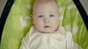 glückliches kleines niedliches Baby schwingen im elektrischen Stuhl Türsteher