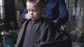 barbeiro aparando cabelo de menino