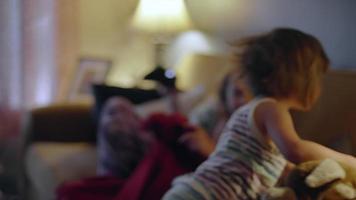 uma menina com um bicho de pelúcia se junta a suas irmãs no sofá sob um cobertor