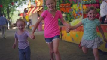 tre bambine che corrono verso la telecamera a un carnevale, rallentatore