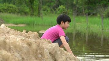 jeune garçon asiatique jouant dans une flaque de boue près de la rivière