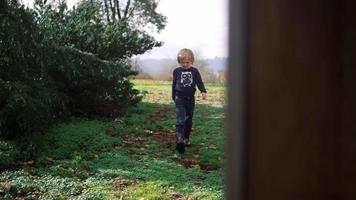 kleines Mädchen, das an einem sonnigen Tag in Zeitlupe durch ein Tor in ihrem Hinterhof geht