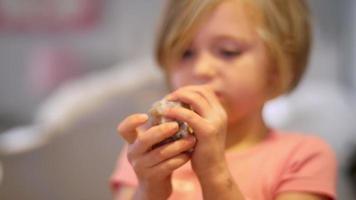 una bambina nella sua stanza mostra una bella roccia della sua collezione, rallentatore