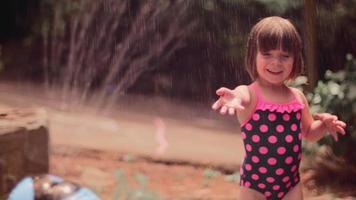 una bambina carina che gioca fuori in un irrigatore
