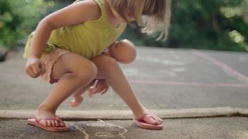 una bambina che disegna sul marciapiede con il gesso