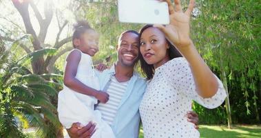 retrato de uma família fofa tirando uma selfie no jardim