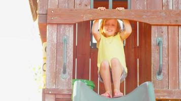 giovane ragazza bionda su una diapositiva all'esterno