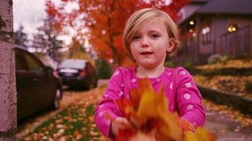 uma garotinha do lado de fora joga folhas de outono no ar e elas caem em câmera lenta