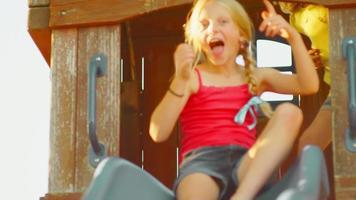 junge blonde Mädchen auf einer Rutsche draußen