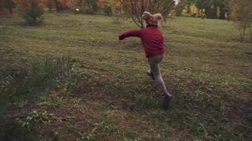 Little girl running in the autumn park or forest video