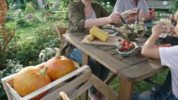 vegane Familie, die Bio-Lebensmittel im Garten isst