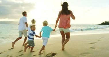 gelukkige familie op het strand bij zonsondergang
