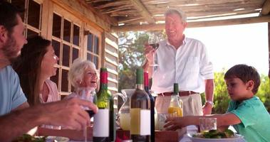 abuelo brindando por su familia en una comida video