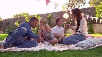 Familia disfrutando de un picnic en una manta en el jardín