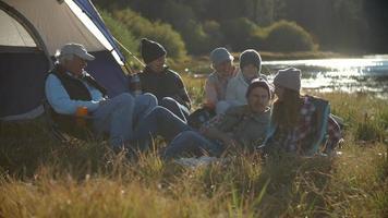 Familia de varias generaciones relajante carpa exterior en el campo video