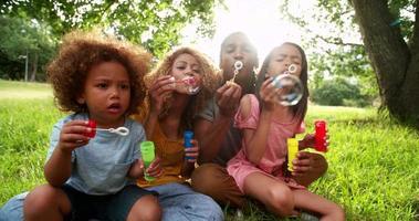 Afroamerikanerfamilie, die im schönen Park sitzt, der Blasen bläst