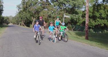 4k família feliz e saudável andando de bicicleta em área residencial