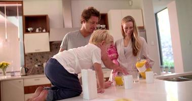 família de quatro pessoas em pé e tomando café da manhã na cozinha
