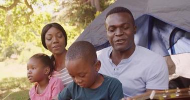 père jouant de la guitare avec la famille devant la tente