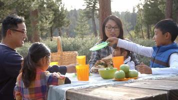 Familia asiática compartiendo comida de picnic en una mesa al aire libre