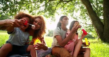 junge attraktive afroamerikanische Familie, die Blasen in der Sonne bläst.