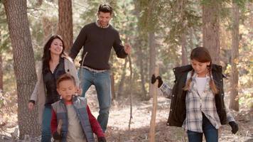 Familia hispana caminatas en el bosque caminar fuera de tiro del lado derecho