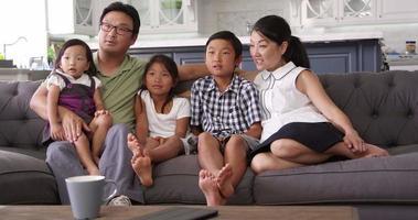 família sentada no sofá em casa assistindo tv no r3d