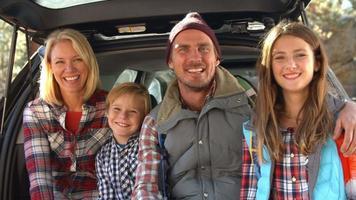 famiglia che si siede nel bagagliaio aperto della macchina, vicino colpo palmare